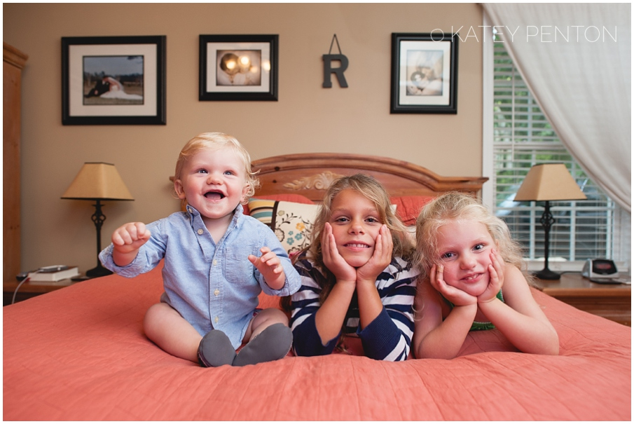 brother and sisters on bed, laughing